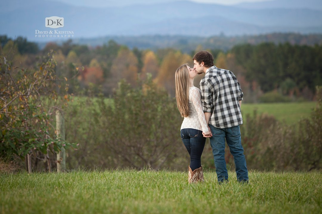 couple kissing at Chattooga Belle Farm with mountain range in the background