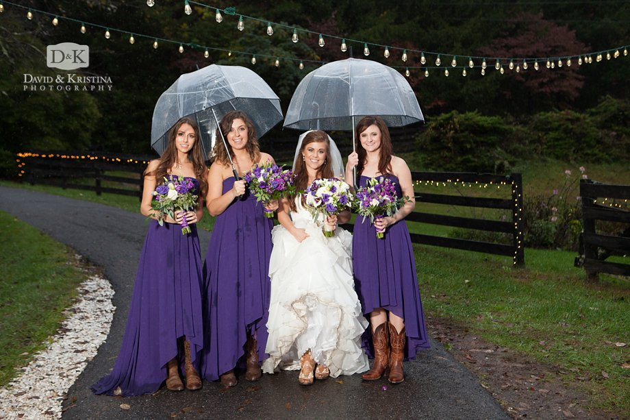 bride and bridesmaids with cowboy boots under clear umbrellas on a rainy wedding day