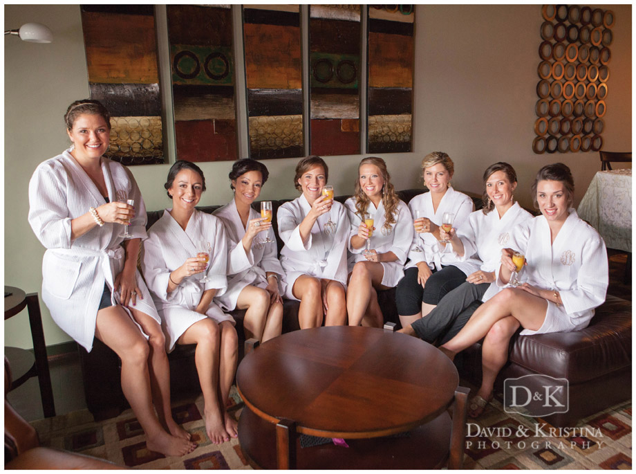bridesmaids in white robes drinking mimosas