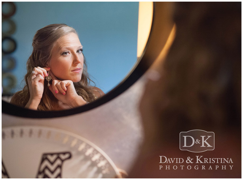 bride putting on jewelry in mirror