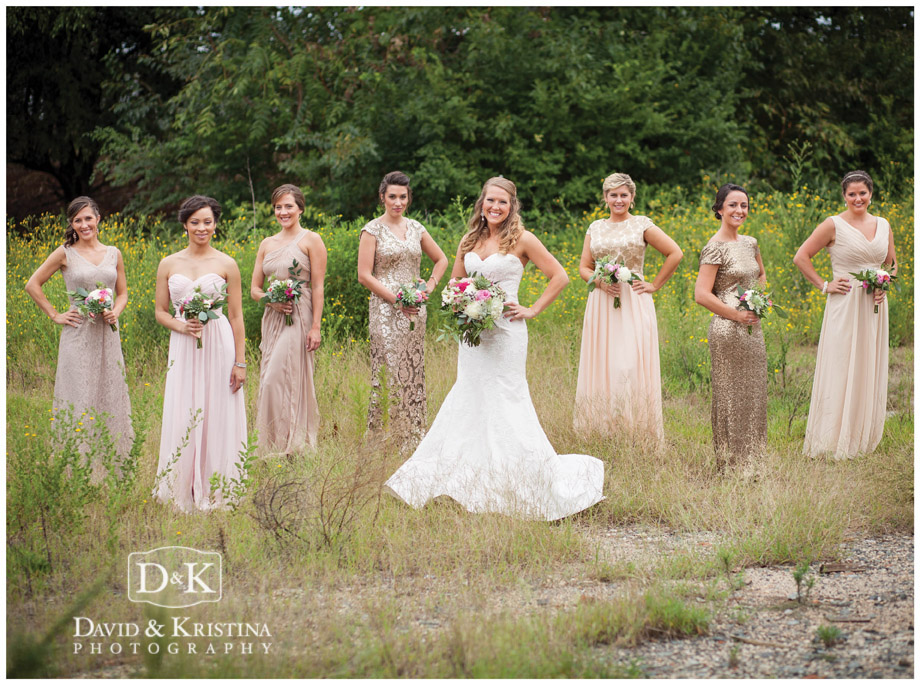 bride and bridesmaids in champaign dresses in field of wildflowers
