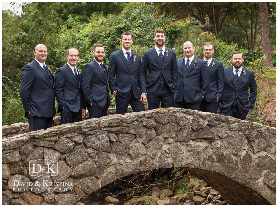 groom with groomsmen in navy suits on stone bridge Rock Quarry Garden