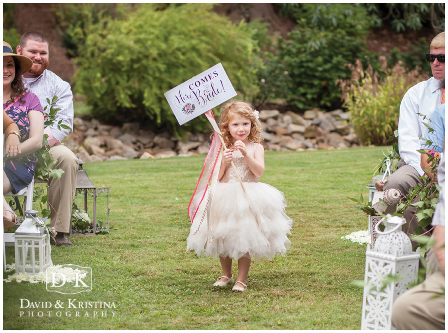 flower girl carrying sign here comes the bride