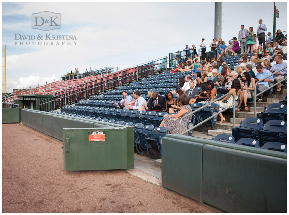 guests awaiting the introduction of bride and groom at baseball field