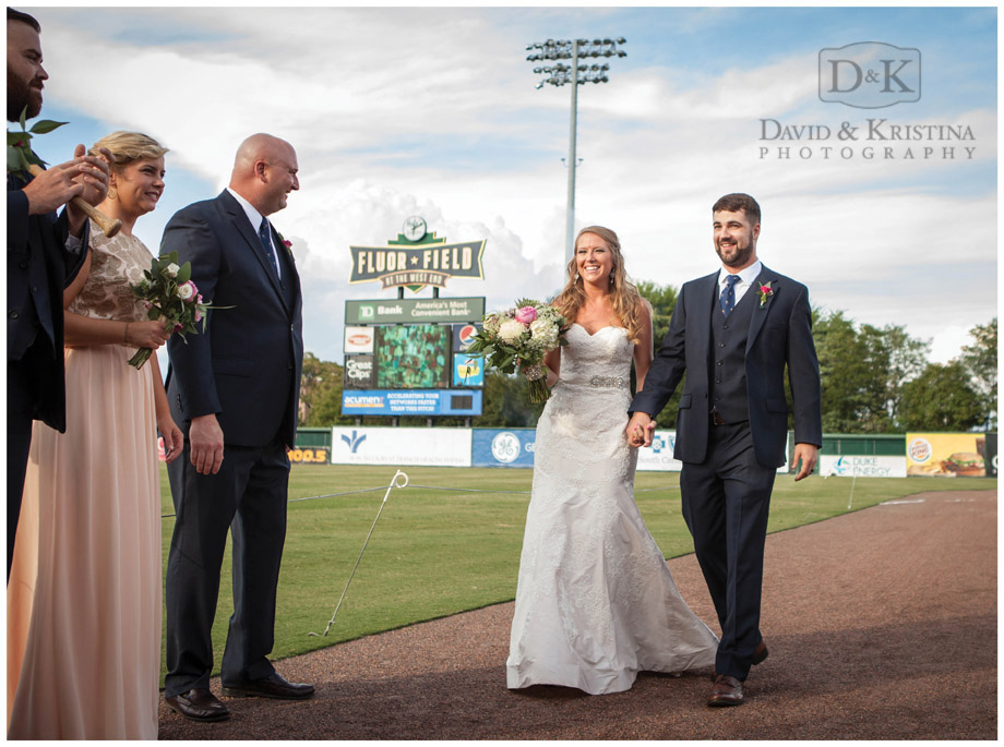 bride and groom walk out onto Fluor Field Greenville Drive baseball field