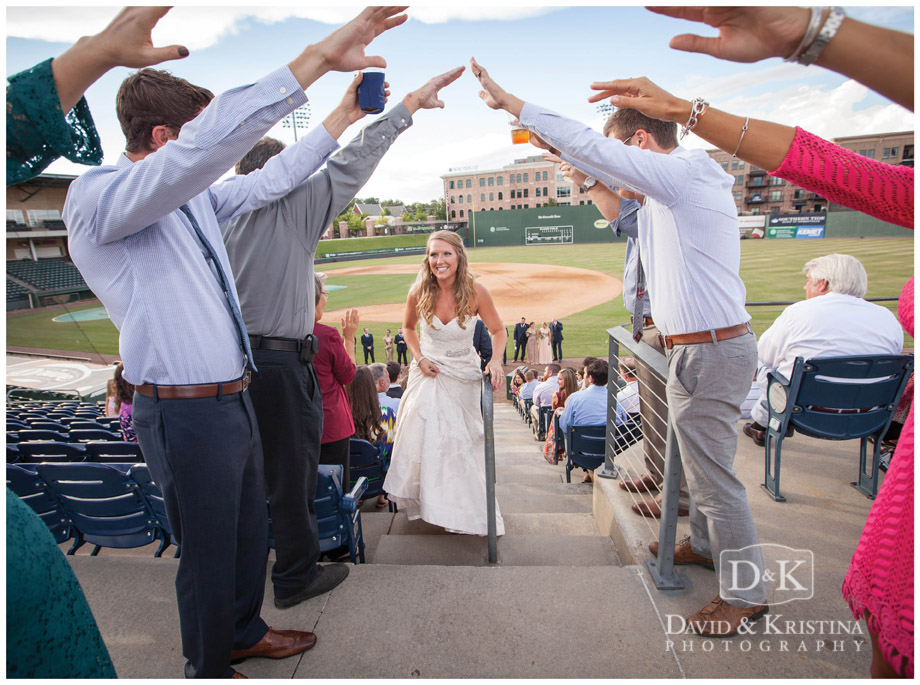 bride walks up steps of baseball stadium