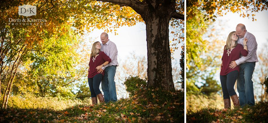 engaged couple standing under a colorful tree