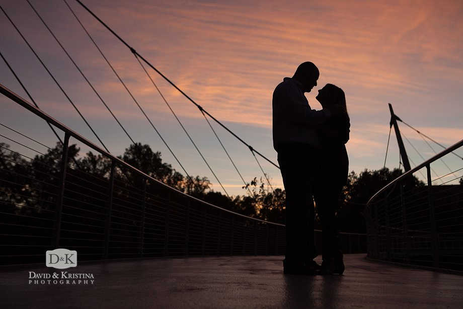 silhouette engagement photo on Liberty Bridge with blue and pink sky