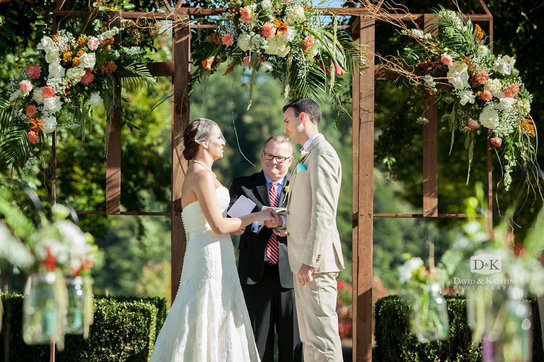 bride and groom exchanging vows under floral arbor at Village Market