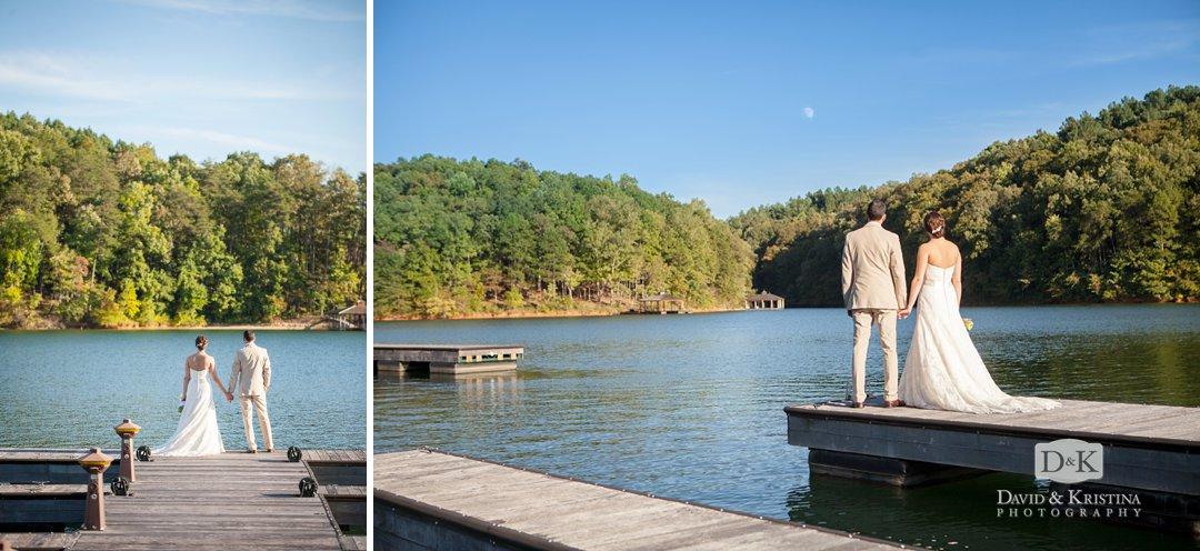 bride and groom standing on dock looking at moon over Lake Keowee