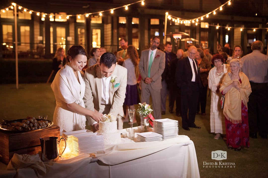 cake cutting under strand lights on the lawn of Orchard Clubhouse at Lake Keowee
