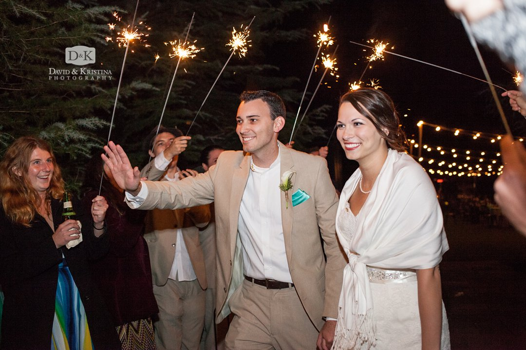 bride and groom walk through sparklers as they exit their reception