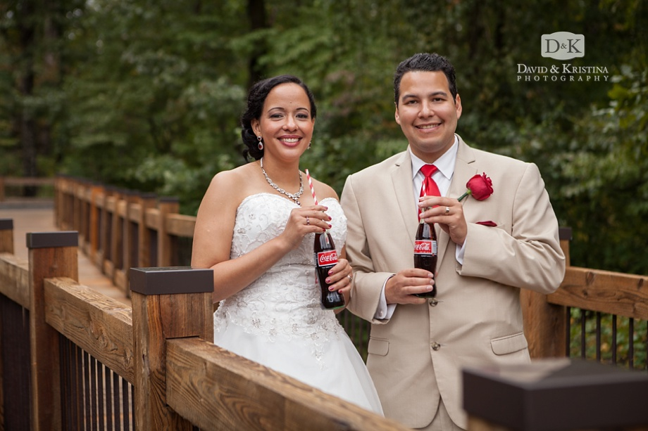 bride and groom drinking coca-cola out of glass bottles with red and white straws