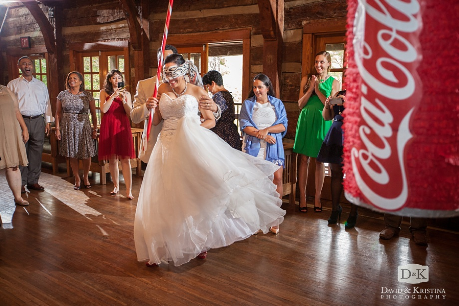 bride blindfolded to hit Coca-Cola can piñata
