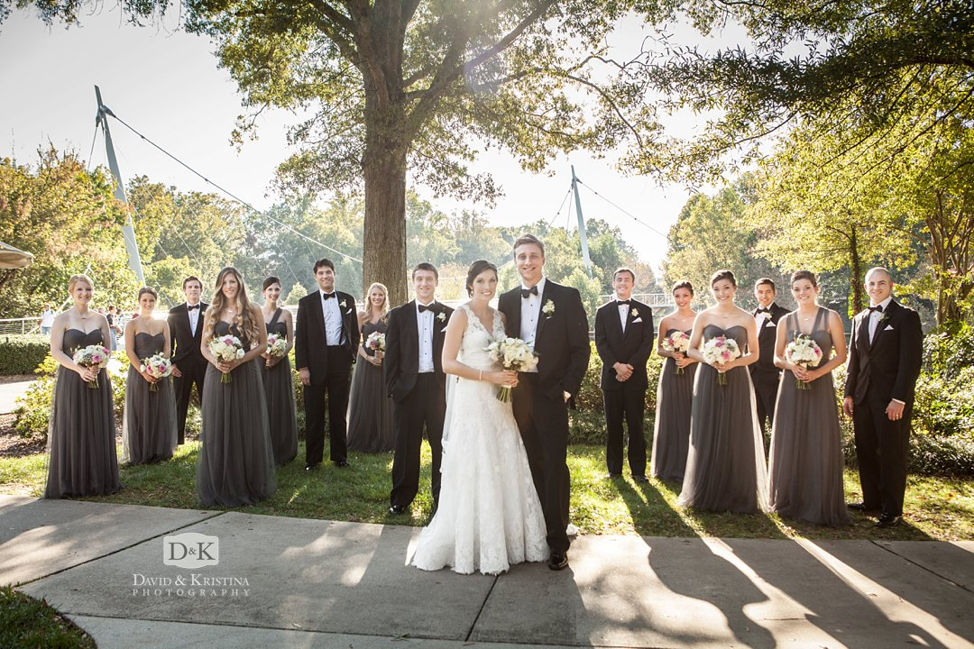 wedding party next to Reedy River with Liberty Bridge in the background