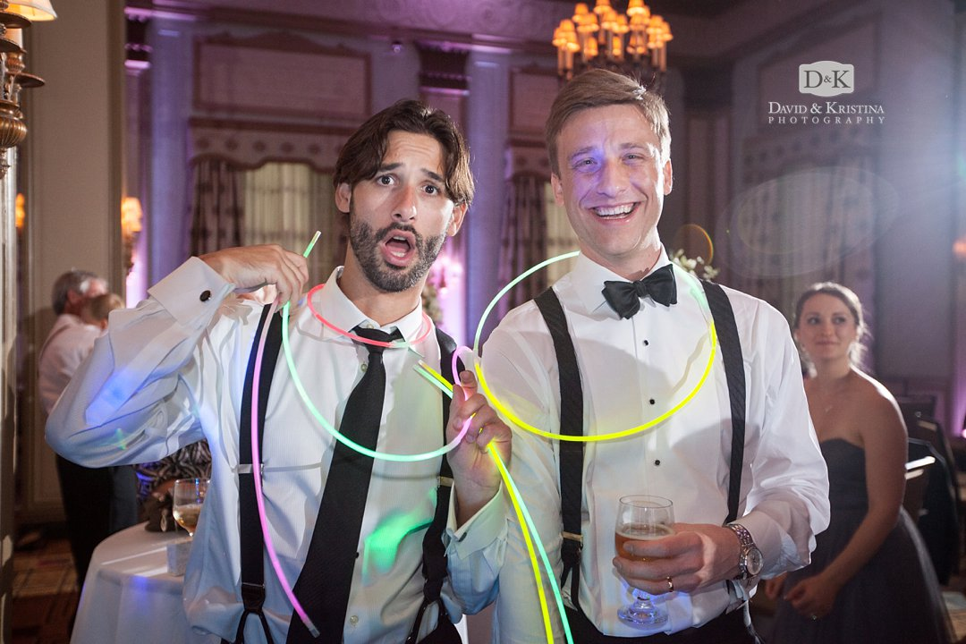 groom and groomsman with glow sticks at wedding reception