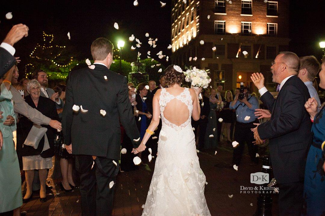 Thomas and Laura walk through flower petal send off downtown Greenville