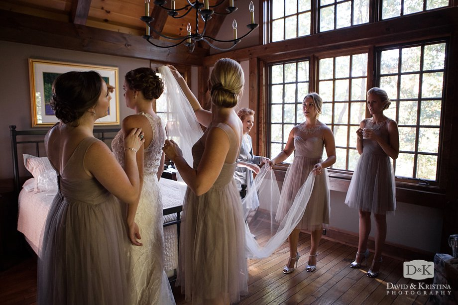 bridesmaids putting on bride's veil