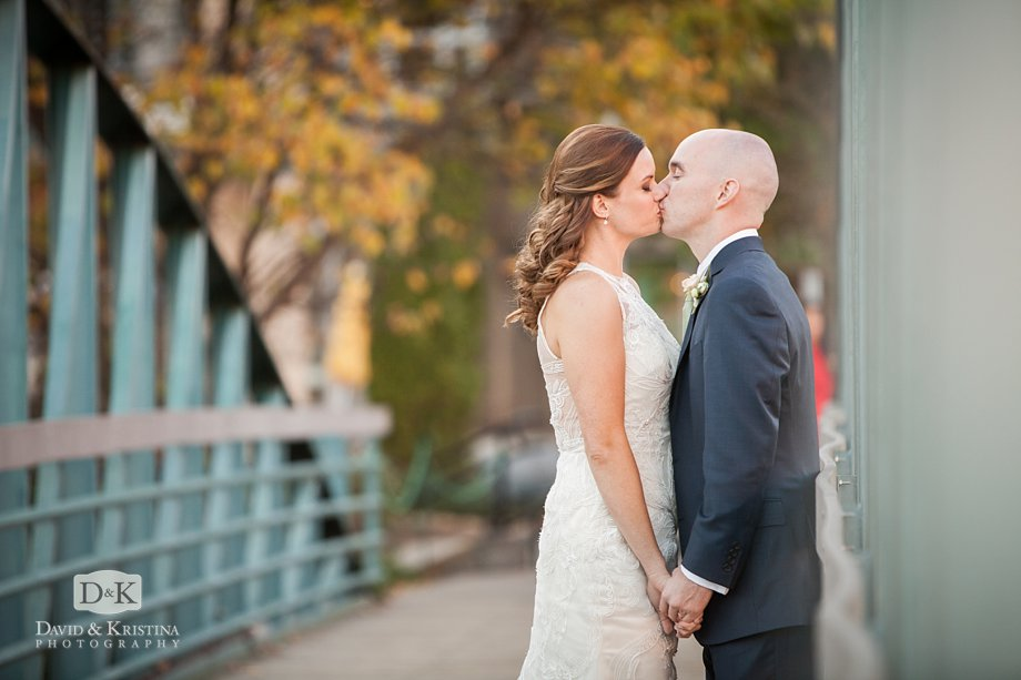 bride and groom kissing on the bridge