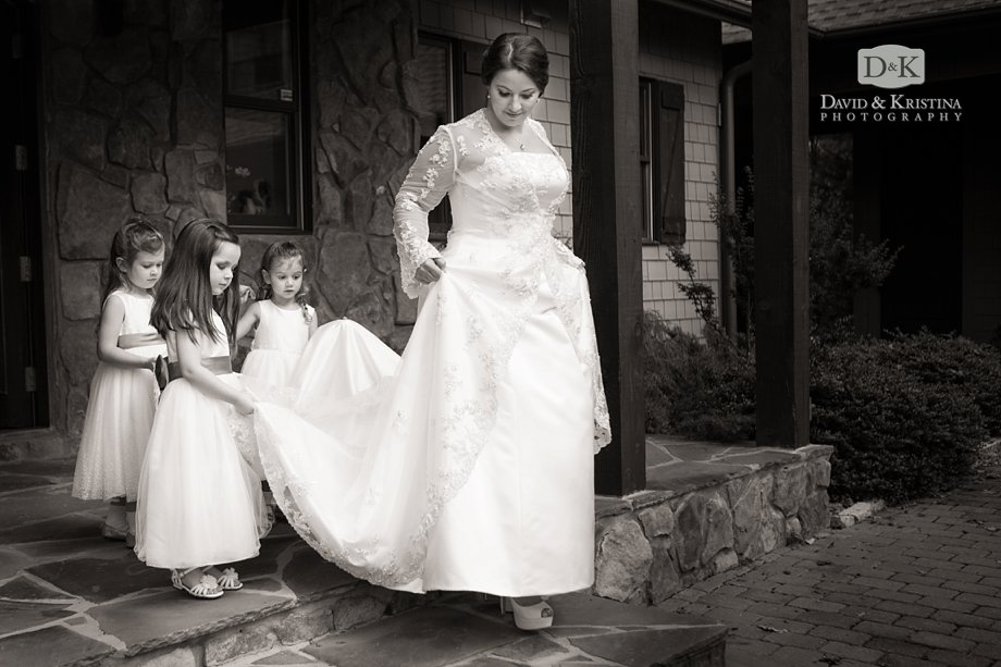 flower girls holding brides dress while walking down stairs