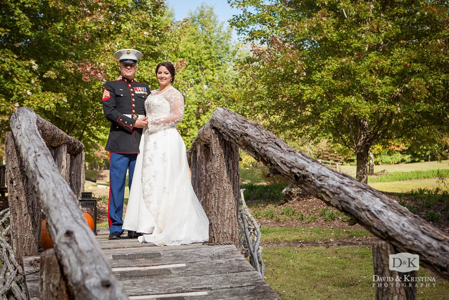 Zak and Meredith on rustic bridge made of branches and rough hewn lumber