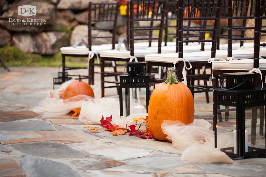 pumpkins and lanterns line the aisle next to chiavari chairs