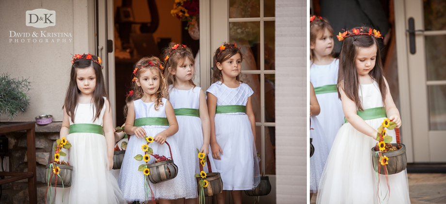 flower girls in white dresses with green sashes holding baskets with flowers