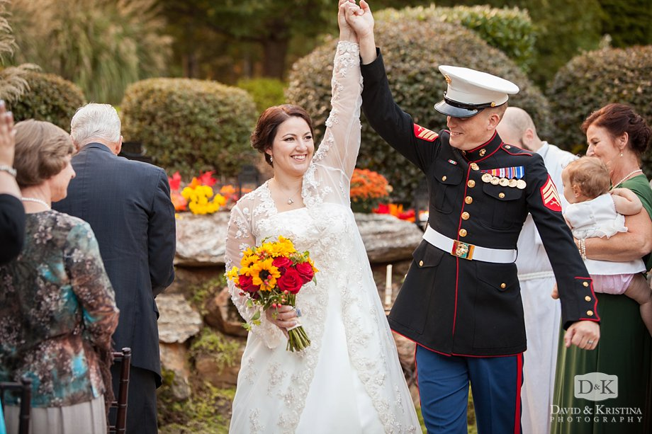 bride and groom throw their hands in the air as they recess up the aisle