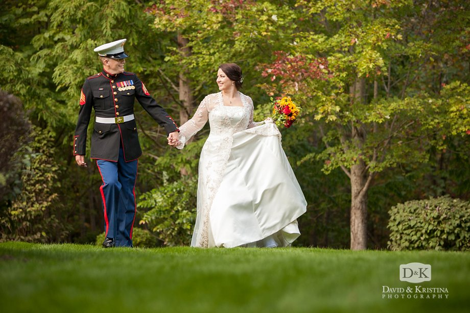 A Marine groom and his bride walk across the lawn