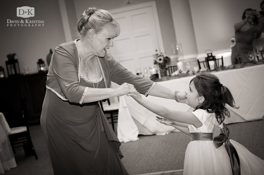 Grooms mother and flower girl dance at wedding