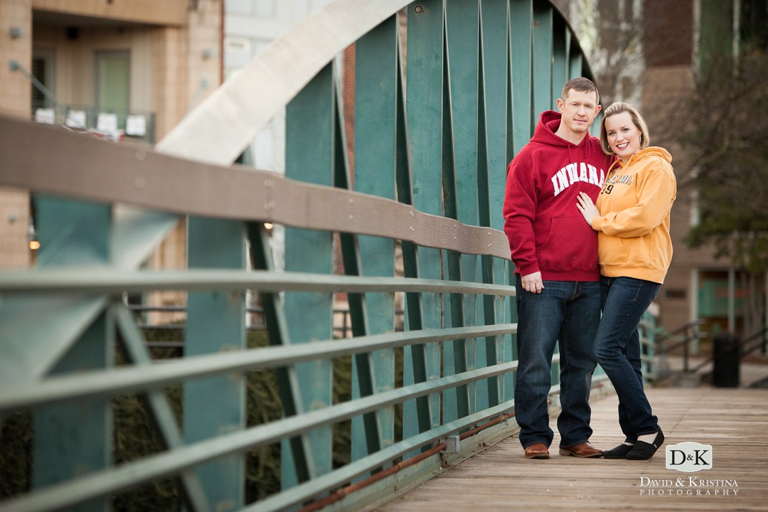 college sweatshirts for engagement photos on Green metal foot bridge over the Reedy River Greenville