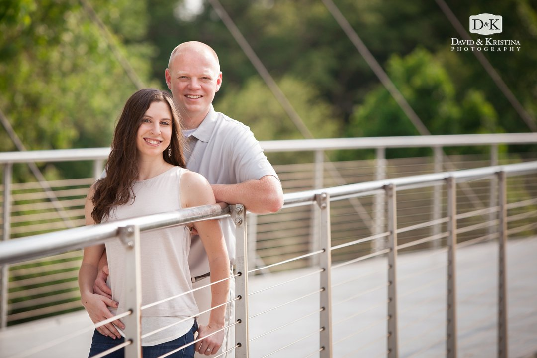 engaged couple standing on Liberty Bridge in Falls Park