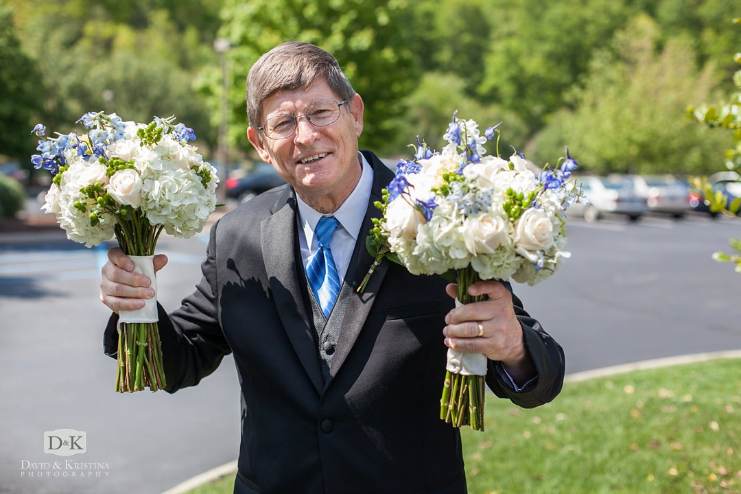 father of the bride holding bouquets