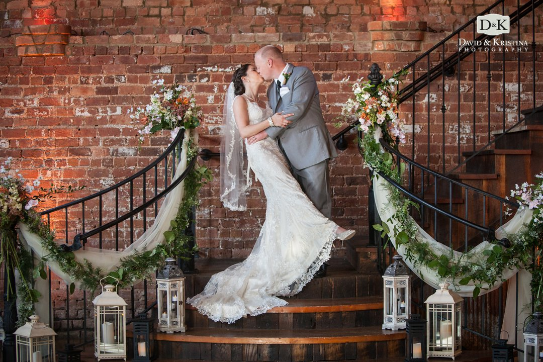 bride and groom kiss on steps at The Old Cigar Warehouse