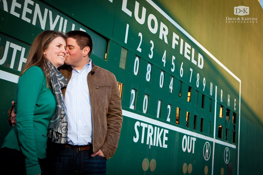 couple kissing in front of Greenville Drive green monster