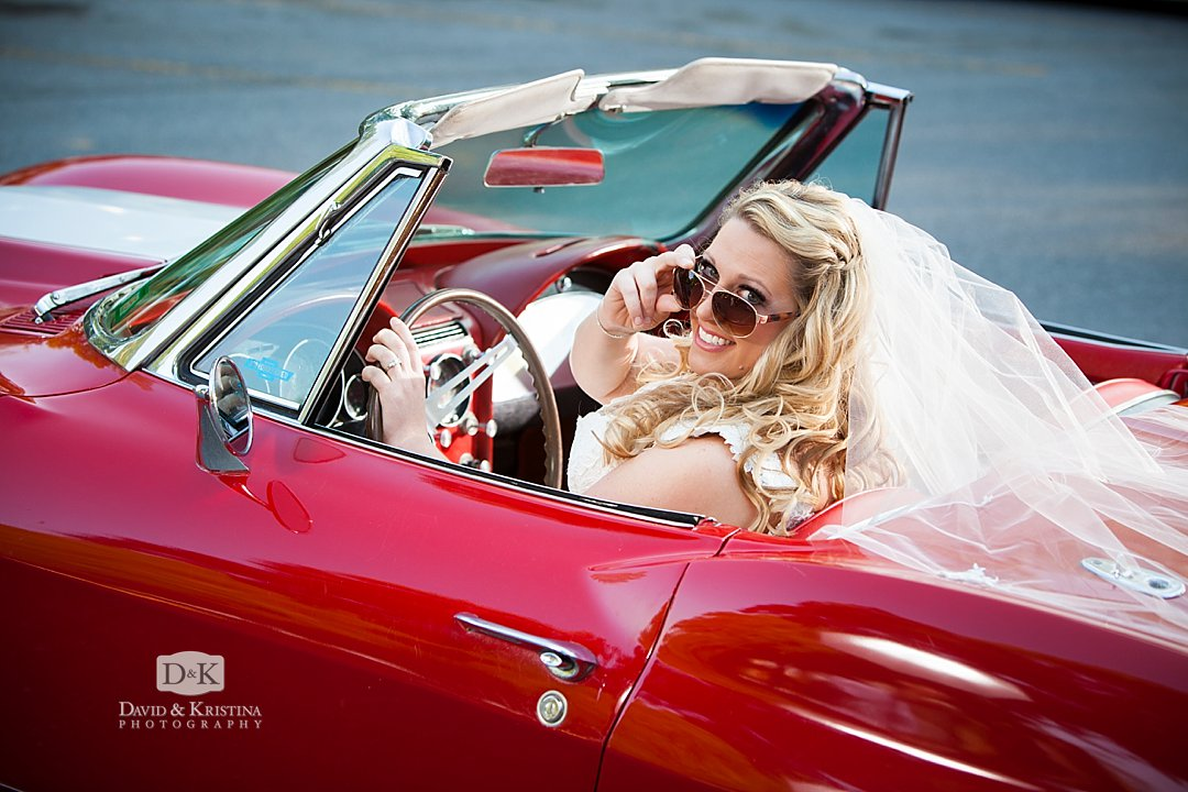 bride in sunglasses driving a red  1965 Corvette