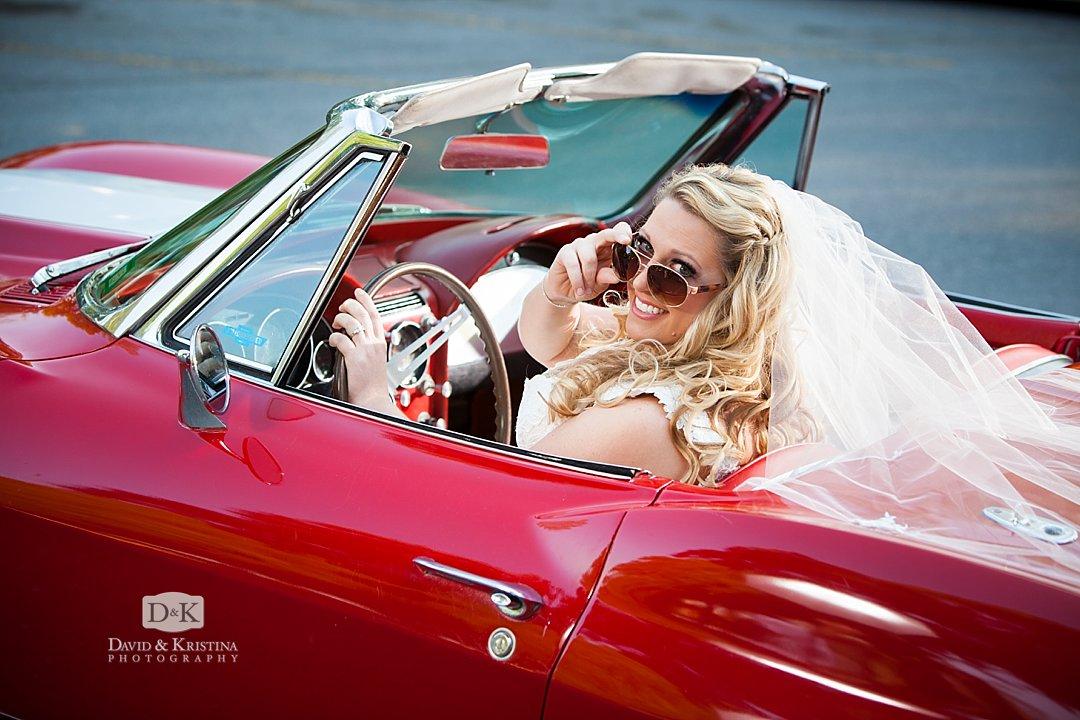 bride in sunglasses driving a red  1965 Corvette