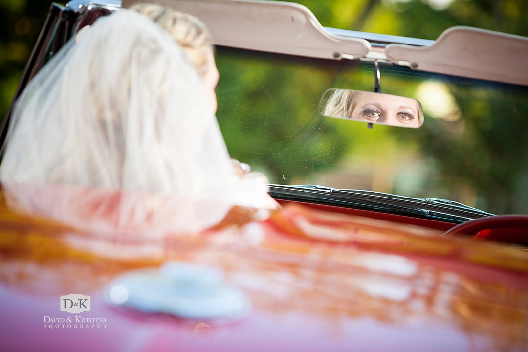 bride looking in rear view mirror of Corvette convertible