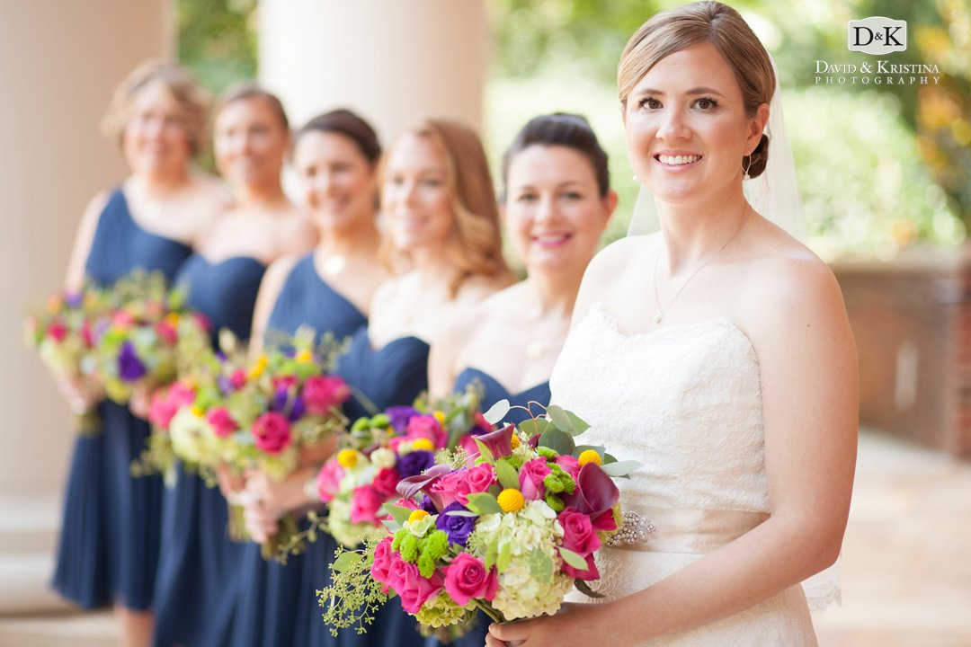 Bride with bridesmaids in Navy dresses with pink, green, and yellow flowers
