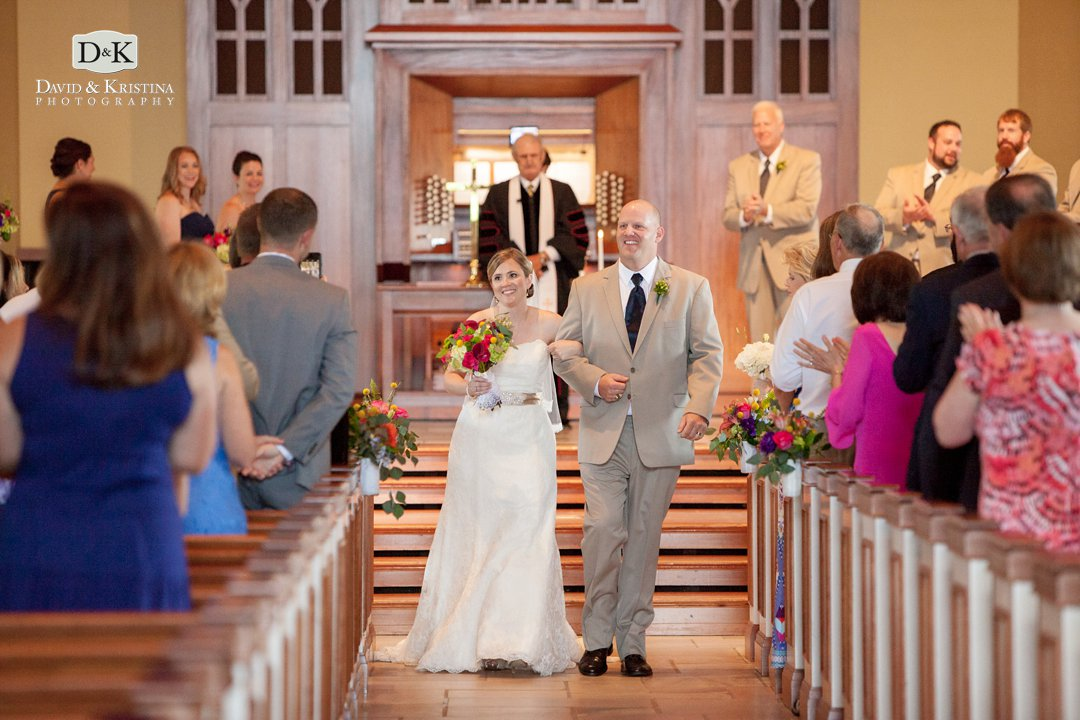 bride and groom recess up the aisle after wedding