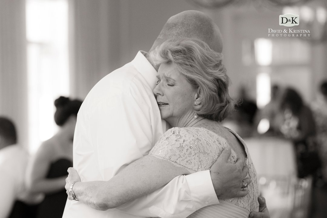 mother hugging son during wedding dance
