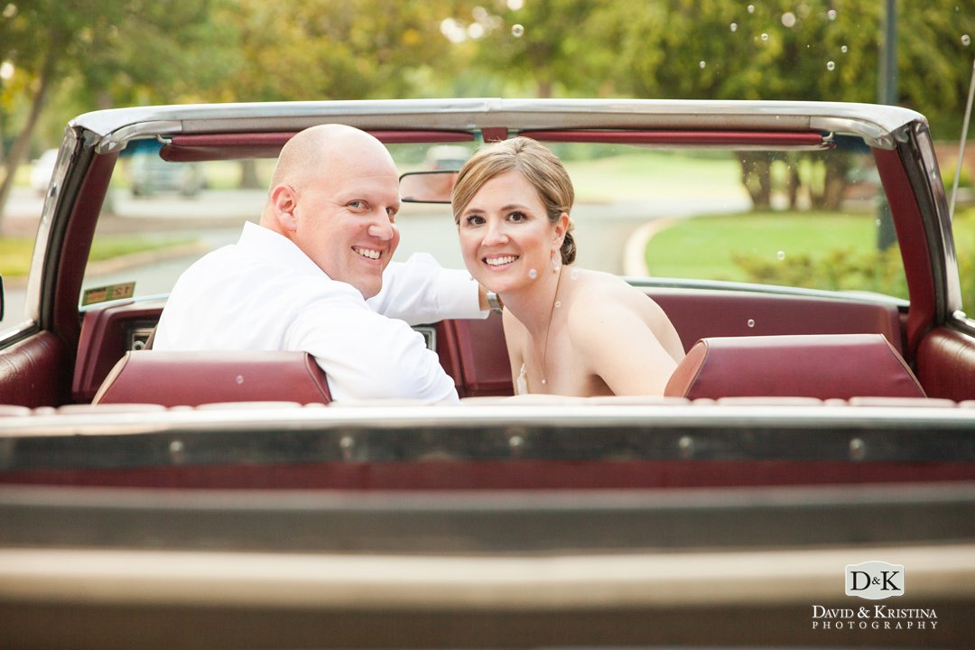 bride and groom leave wedding in old convertible
