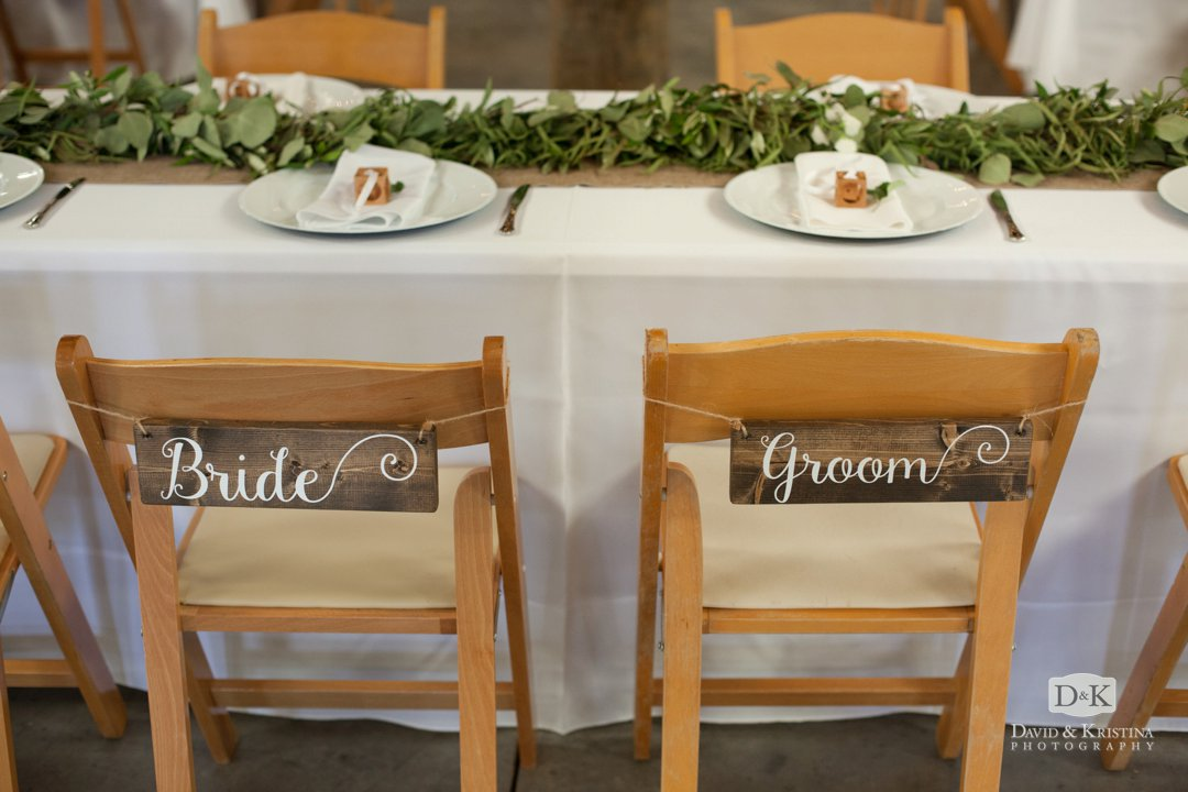 wooden bride and groom signs on back of chairs
