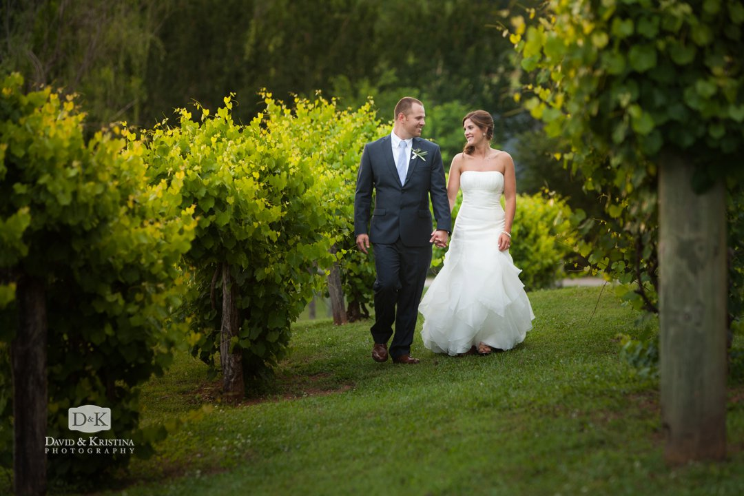 bride and groom walking in vineyard at Greenbrier Farms