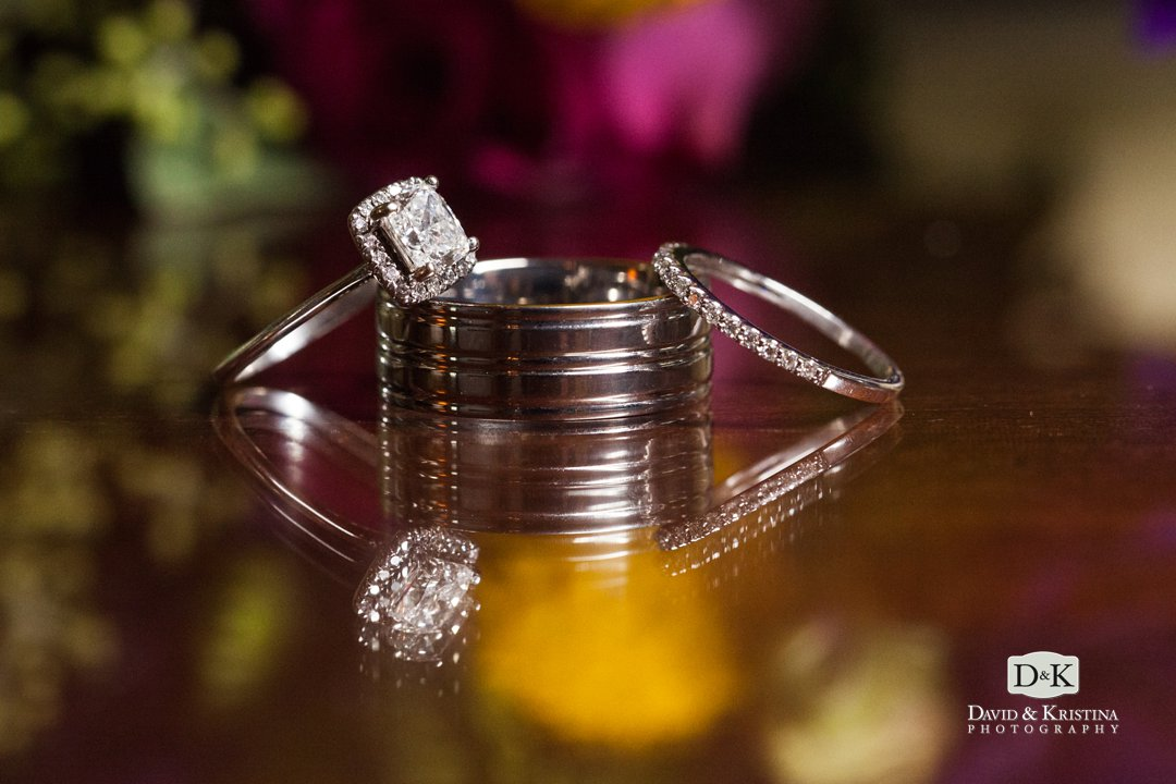 wedding rings with reflection and flowers in background