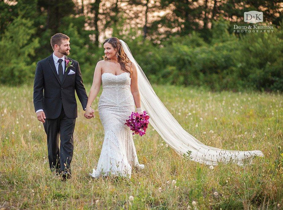 bride and groom walk in field