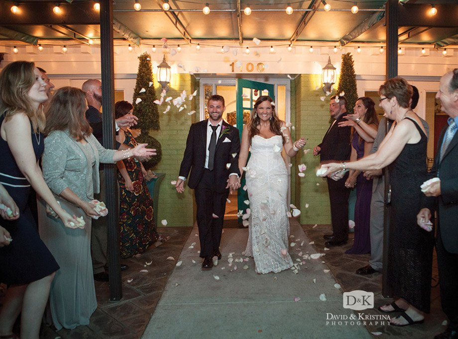 bride and groom exit with rose petal flower toss