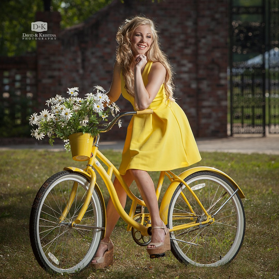 vintage yellow bicycle with a basket of white daisies