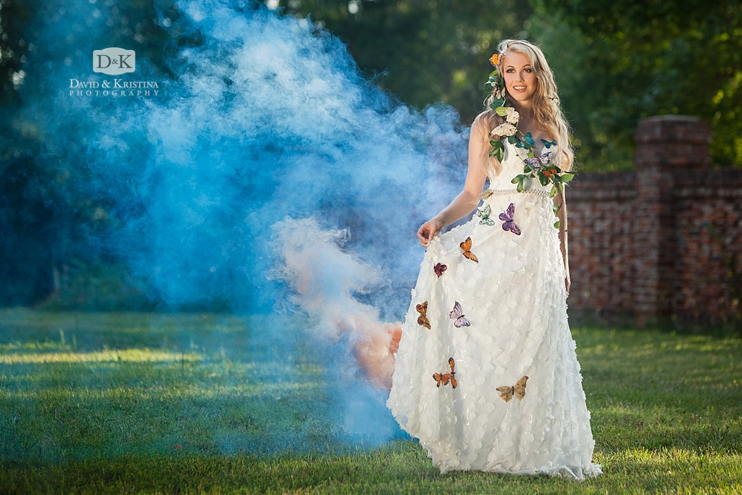 senior portrait with colored smoke bombs and butterflies