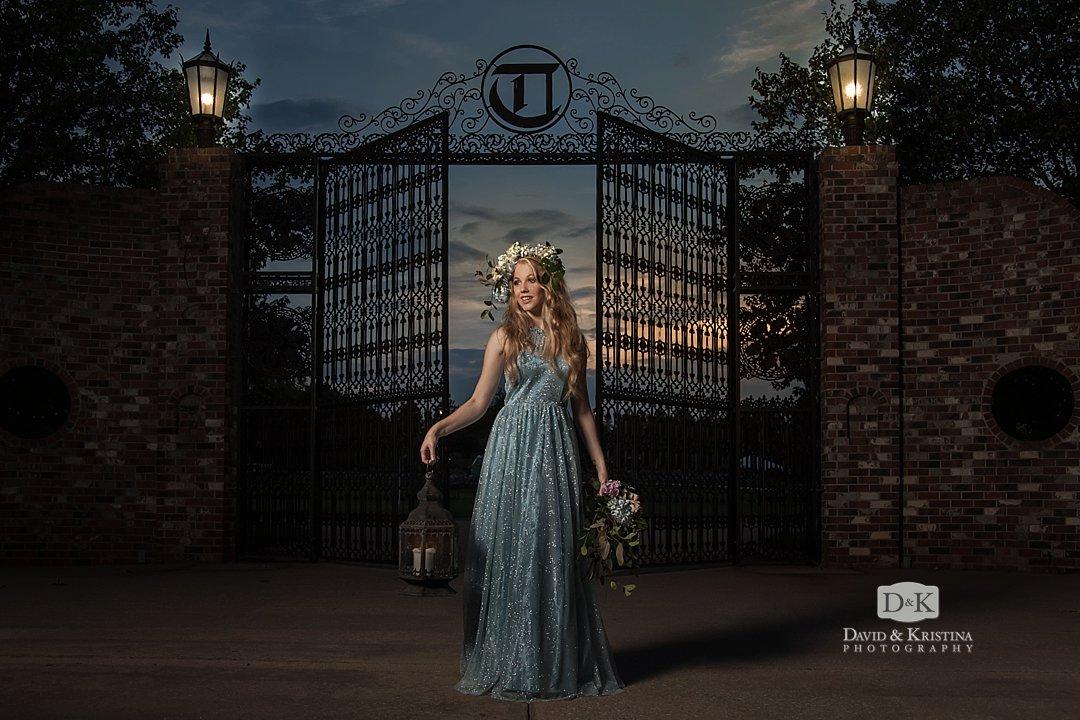 girl in flower hair piece holding lantern in front of iron gate at Edinburgh West
